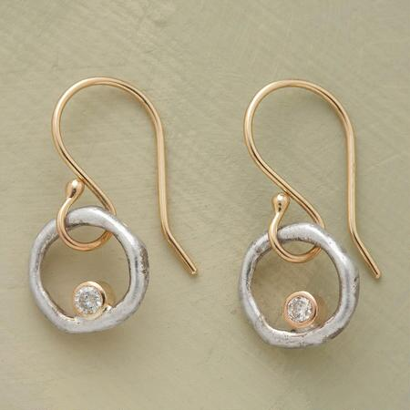 A pair of handmade diamond and silver loop earrings, designed to allow the jewel to swing and sparkle.