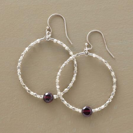 These heartbeat garnet hoop earrings accent the sterling hoop design with a glowing touch.