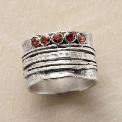 With dramatic lines and rich color, this sterling silver garnet ring delivers a dash of allure.
