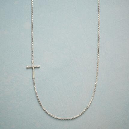 A small sterling cross necklace that draws the eye with its unusual design.