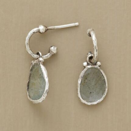 A pair of silver hoop-set aquamarine earrings that captures light from before and behind.