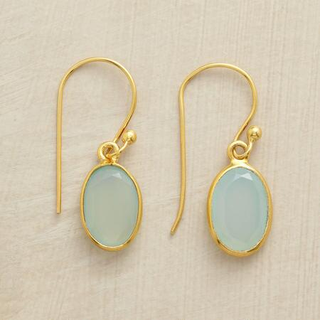 A pair of golden rimmed chalcedony earrings that exudes a serene luminescence.