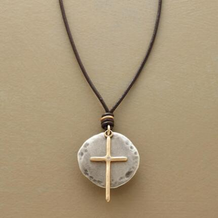 The silver background of this diamond-set cross necklace highlights the central symbol's beauty.