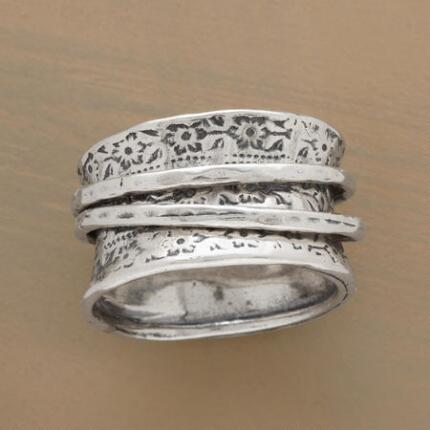 This magic carpet spinner ring's embellished band and lively movement make it a unique treasure.