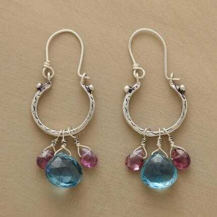 This pair of blue topaz and garnet hoop earrings casts off a shimmering light as it sways.