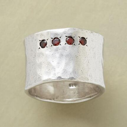 With a bold band and diminutive detailing, this starburst-set silver garnet ring is a delight.