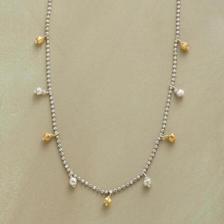 This silver and gold bead necklace brings a touch of delicate contrast to any look.