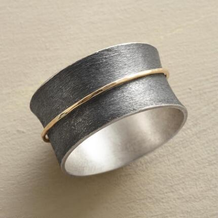 This handmade 14kt gold band spinner ring contrasts bright elements with dark, bold with delicate.
