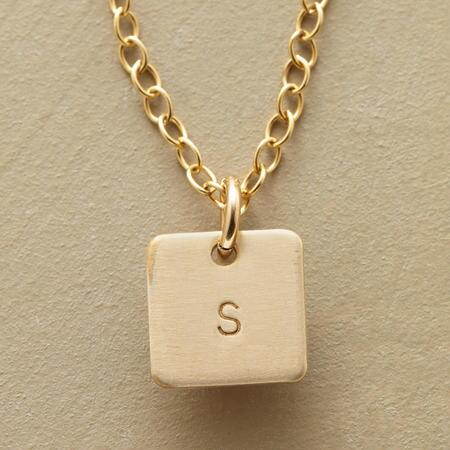 This golden initial pendant necklace lends a subtly personalized style to your look.