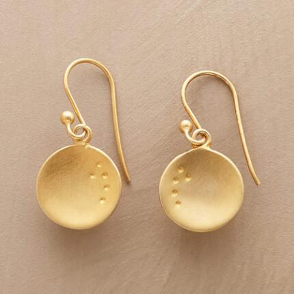 This pair of dangling golden disc earrings charms with its open glow.