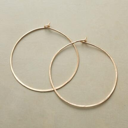 A pair of hand-hammered golden hoop earrings that bring a subtle distinction to this classic design.