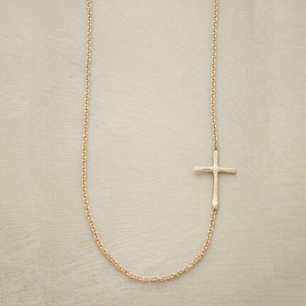 This small gold cross necklace has a uniquely delicate design that wears well with anything.