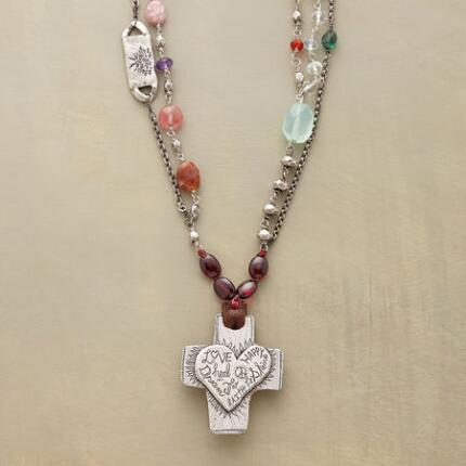 A Jes MaHarry gemstone cross necklace decorated with messages and materials that radiate happiness.