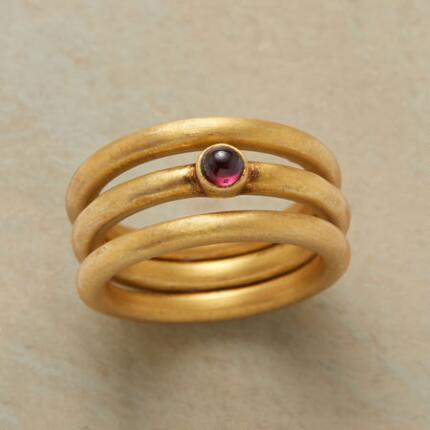 The ample gold bands of this garnet triple ring set make its single stone shine all the brighter.