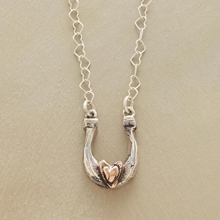 Lovingly handcrafted, this heart and horseshoe necklace is a perfectly pretty talisman.