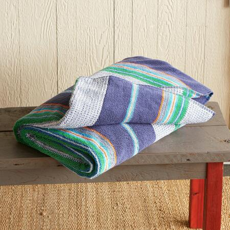 Lie out on this blue striped cotton beach towel, or wrap up in it—you'll love it either way.